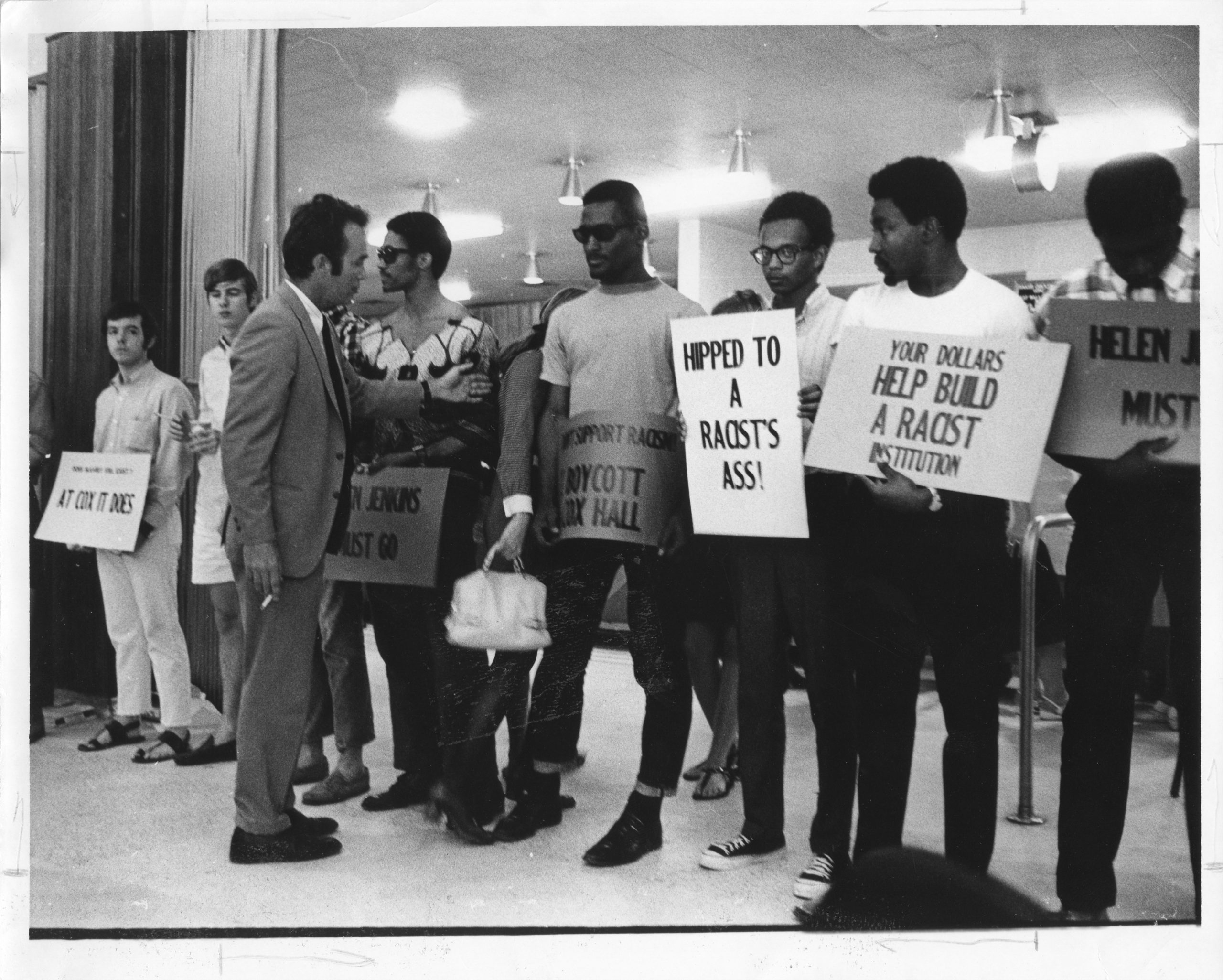 """Photo of student protestors holding signs, including """"your dollars helped build a racist institution"""""""