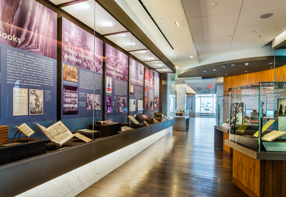 Photograph of exhibit space with glass display cases featuring books, images, and descriptive text