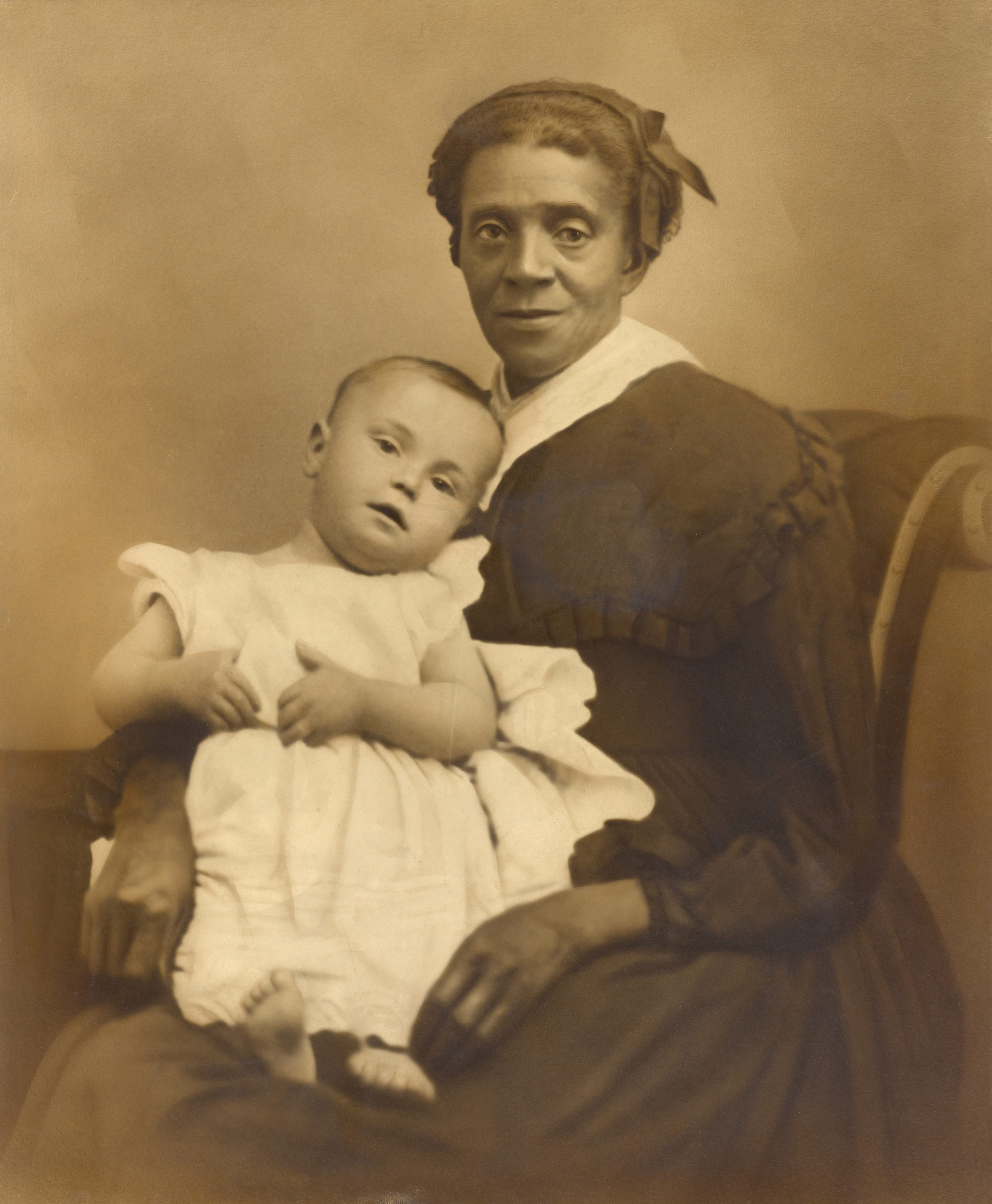 Photograph of child with light skin tone being held by woman with medium-dark skin tone.
