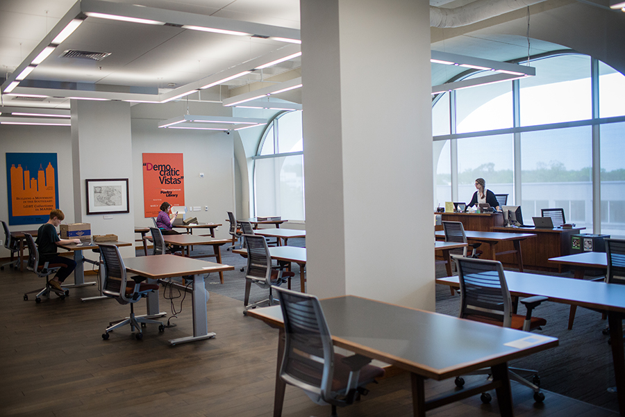 Brightly lit reading room with several rows of desks and chairs