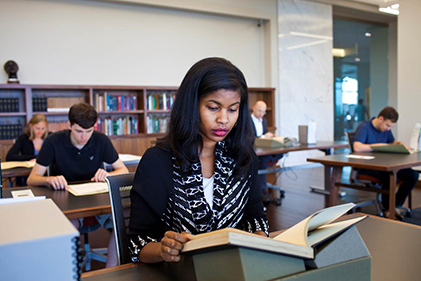 People reading at rows of large desks in front of bookshelves in Rose Library reading room